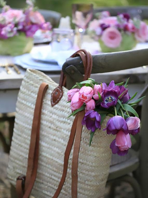 kreative osterdekoration mit rosa- und lilafarbigen tulpen in einer tasche als originelle stuhldeko