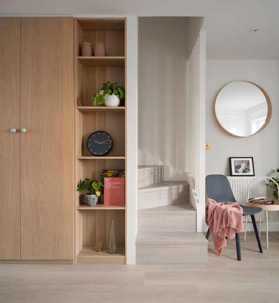 gemütliche kleine wohnung im skandinavischen stil platzsparend und sinnvoll einrichten durch einbauholzschrank mit regalen als zusätzlicher stauraum unter treppe