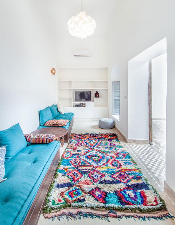 orientalische zimmereinrichtung ideen_kleines wohnzimmer in weiß fröhlich einrichten mit holzsitzbänken, blauen polstern und buntem teppich