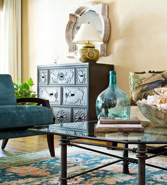 attraktive wohnzimmer einrichtung mit orientalischem charme durch die kombination vom alter holzkommode, spiegel in silberrahmen und blauen textilien