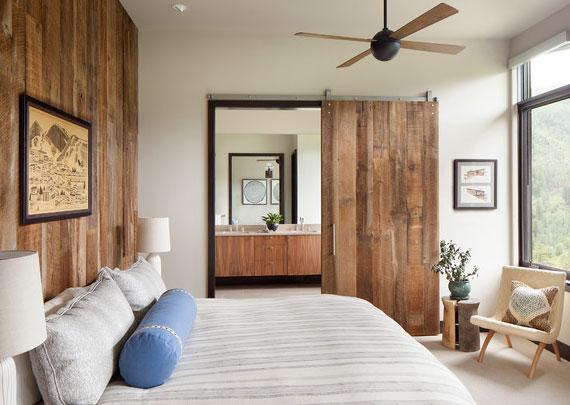 rustikales schlafzimmer interieur mit holzwandverkleidung hinter bett und durchgangszarge mit schiebetür aus holz als platzsparende zimmertür zwischen bad und schlafbereich