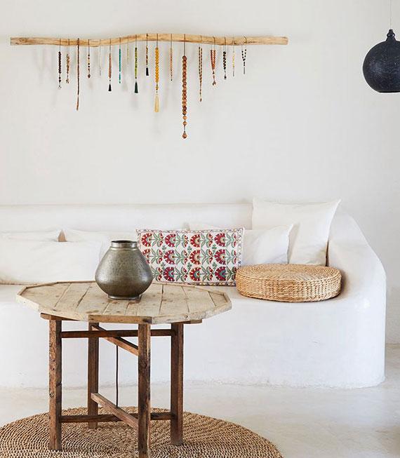 DIY Wandkunst aus treibholz und bunten holzperlen für elektrische und lebendige verzierung der wand hinter einem weißen sofa