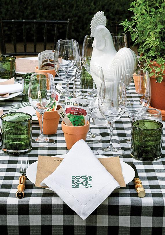 Gartentisch für eine Pizza Party passend eindecken mit karierter Tischdecke, wassergläsern in grün und frischen Topfkräutern