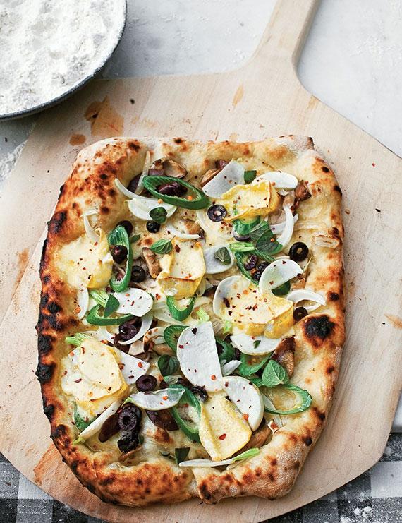 hausgemachte pizza mit Oliven, Basilikum-Pesto, Rettichscheiben, Fenchel und Frühlingszwiebel