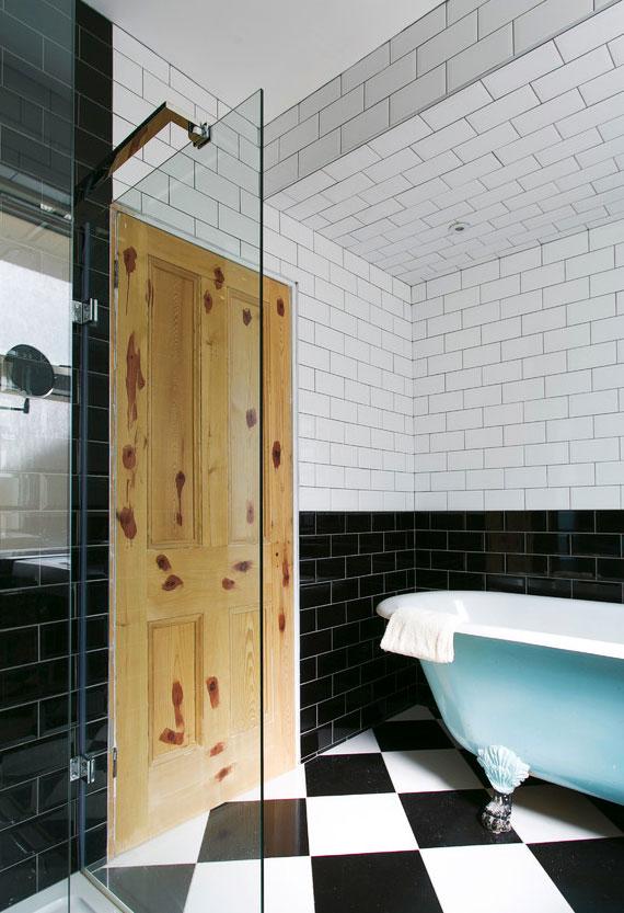schickes Bad interieur design in schwarz und weiß mit zimmertür aus massivholz und freistehender badewanne in hellblau