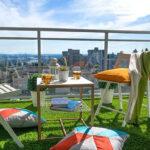 balkon und terrasse für die sommerzeit vorbereiten und mit einem grünen bodenbelag fröhlich gestalten