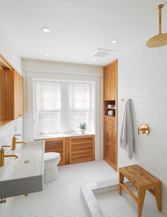 attraktives baddesign in weiß mit einbauschrank aus holz unter fensterbank und in wandnische