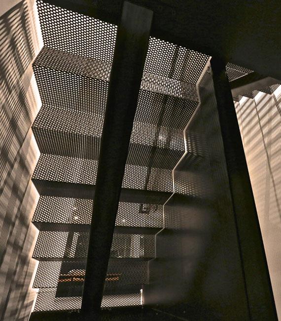effektvolle Lichtgestaltung im Raum durch das moderne Treppendesign einer zweiläufigen Innentreppe mit Lochblechstufen