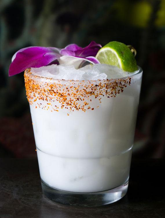Bodega Negra Cocktail in Glas mit gewürztem Rand servieren und mit essbarer Blüte und Limettenscheibe garnieren