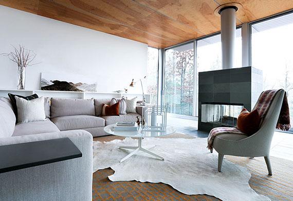 ein wohnzimmer gemütlich gestalten im skandinavischen Hygge Wohnstil mit kuscheligen Decken und weißem kuhfell teppich