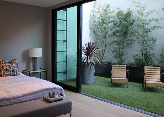 modernes schlafzimmer mit schiebetür zur kleiner begrünter terrasse mit kunstrasen, dekorativen bäumen und holzliegestühlen