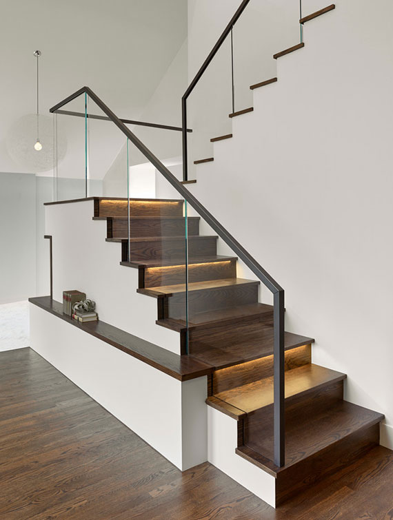 schlichtes treppendesign mit dunkler Kolzverkleidung, Glasgeländer und indirekter Stufenbeleuchtung