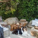 wohnliche sitzecke in einem küstengarten mit stühlen aus felsen und couchtisch aus großem baumstamm