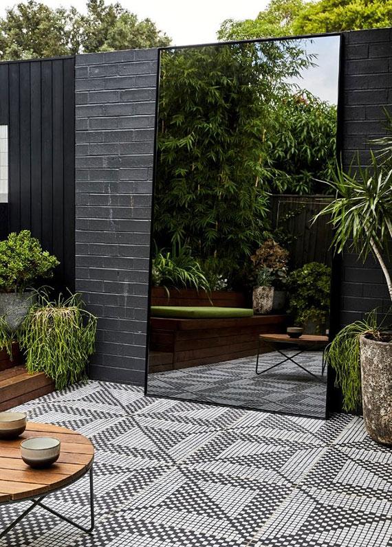 großformatiger Außenspiegel in schwarzem rahmen als attraktives gestaltungselement in einem modernen gartendesign
