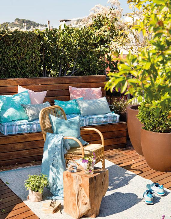 attraktive terrassen deko mit farbenfrohen kissen,teppich und diy baumstamm-tisch
