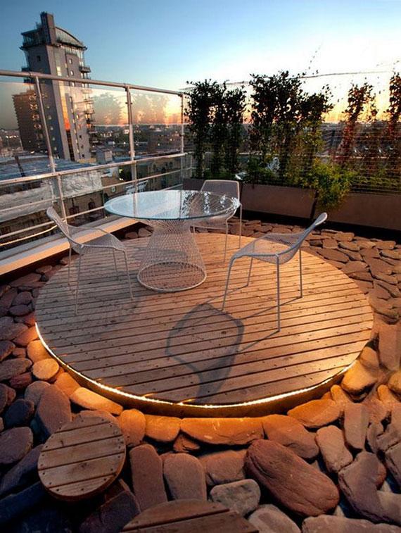 effektvolle terrassengestaltung einer dachterasse mit kiesboden, sitzecke auf holzpodest mit indirekter beleuchtung und sichtschutz mit pflanzen