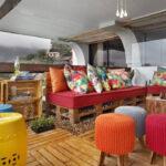coole einrichtungsidee für farbenfrohe Terrasse mit holzboden, palettenmöbeln und bunten hockern