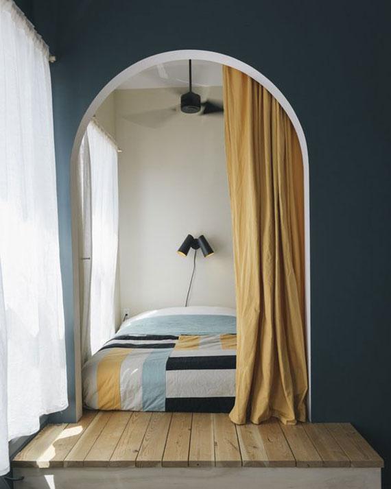 eine gemütliche schlafecke im zimmer definieren durch grün gestricheneTrennwand mit gewölbter öffnung und gelbem forhang