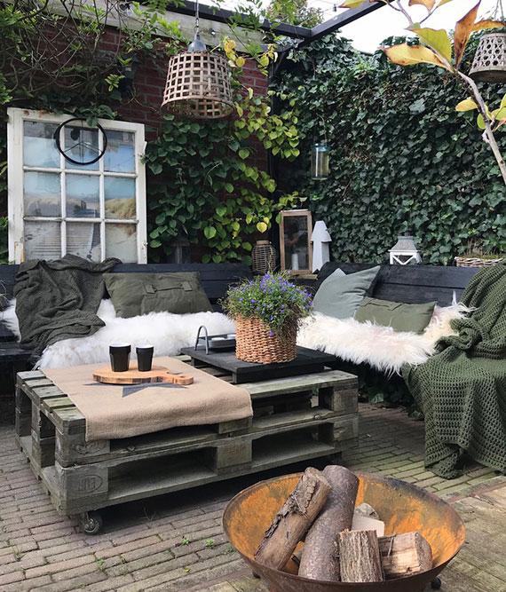 mit DIY Gartenmöbel aus Paletten, kleiner Feierstelle und kuscheligen Kissen eine gemütliche sitzecke im Herbst draußen gestalten