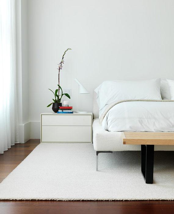 modernes schlafzimmer interior in weiß mit passendem teppich nach maß unter bett und nachttischen