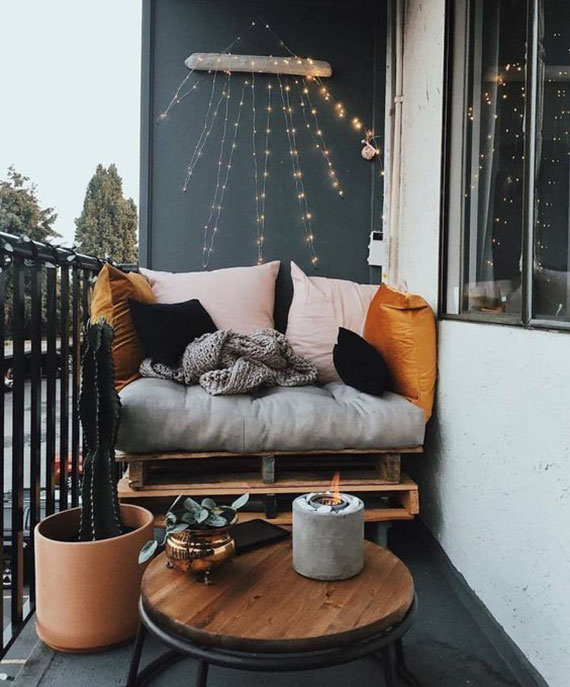 moderne terrassengestaltung in dunkelgrau mit palettensessel, kleinem holzbeistelltisch rund und bunten kissen für farbakzent