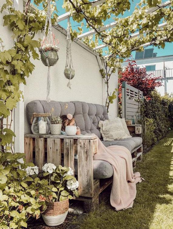 romantische sitzecke im garten schaffen mit einem DIY Gartensofa aus paletten unter begrünter pergola mit kletterpflanzen