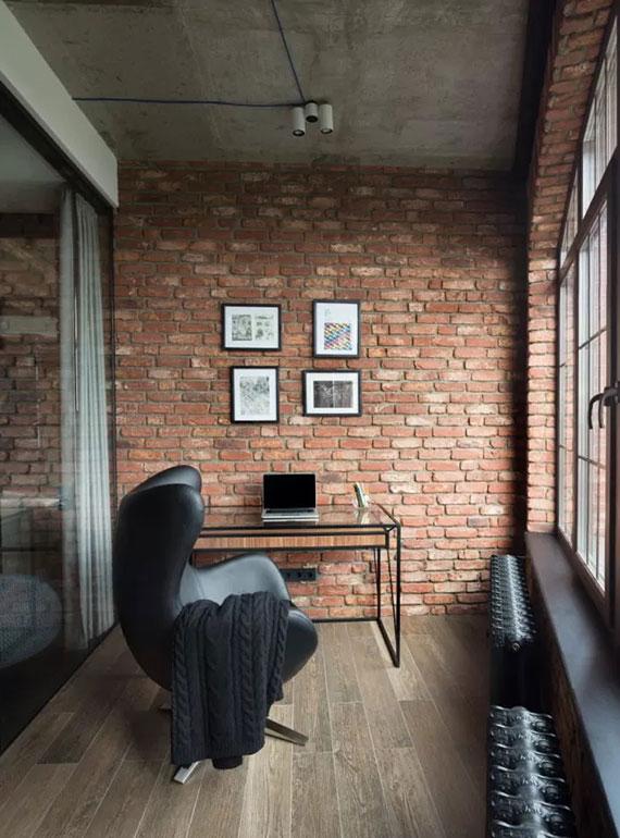 moderne gestaltungsidee für ein homeoffice auf der loggia mit holzboden, ziegelwänden und schwarzen heizkörpern unter den fenstern
