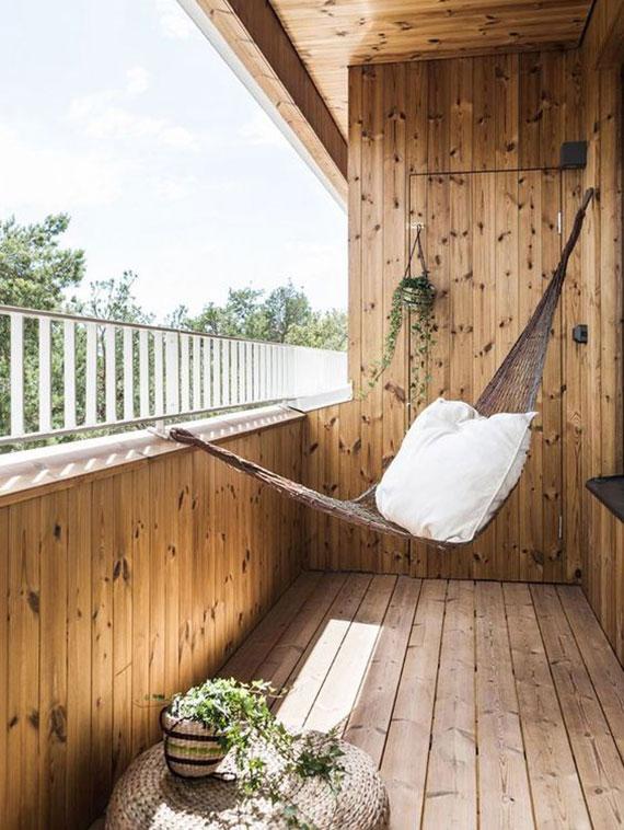 der kleine balkon gemütlich und wohnlich gestalten mit holzverkleidung und einer hängematte, aufgehängt zwischen pfosten und wand zwischen