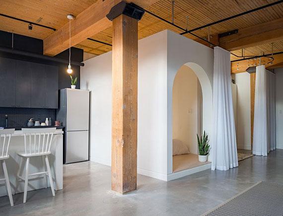 modernes studio apartment mit offenem grundriss und einem weißen Kubus mit Vorhang für den Schlafbereich