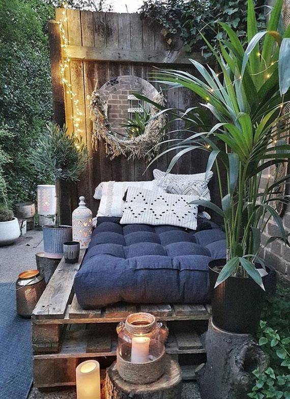 geheime Ruheecke im garten gestalten mit einer DIY Gartenliege aus paletten und polstern, vielen Windlichtern und Grünpflanzen in Kübeln