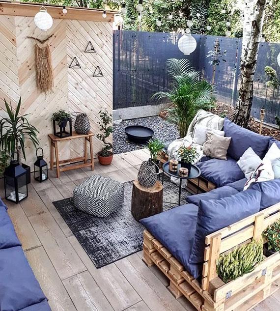 frische garten lounge ideen für gemütliche sitzecke im garten mit einem palettensofa, blauen polstern und zahlreichen laternen