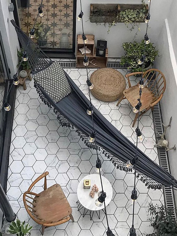 Terrasse oder Hofgarten stilvoll gestalten mit weißen Hexagon Fliesen, Rattanmöbeln und schwarzer tuchhängematte