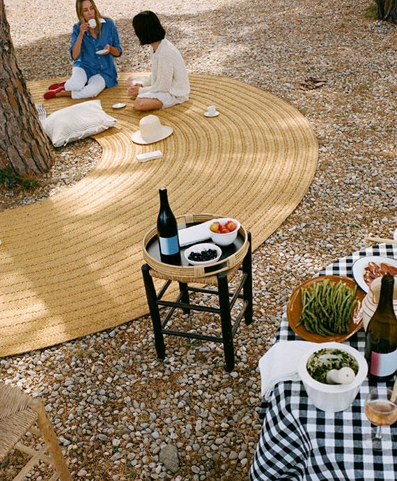 coole Sitzecke im Garten, Park oder Wald schaffen mit einer aus Naturfasern geflochtenen Teppichmatte