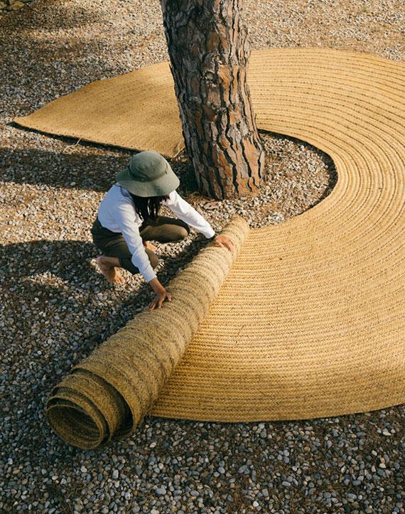 der handwebteppich Oráculo ist eine kreisförmige Matte aus Espartogras und bildet eine gemütliche sitzecke unter bäumen