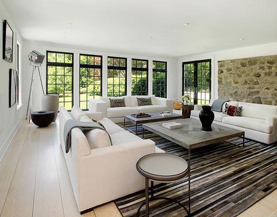 modernes wohnzimmer interior design mit historischem Charme dank rustikaler Holztische und einer Stein-Akzentwand