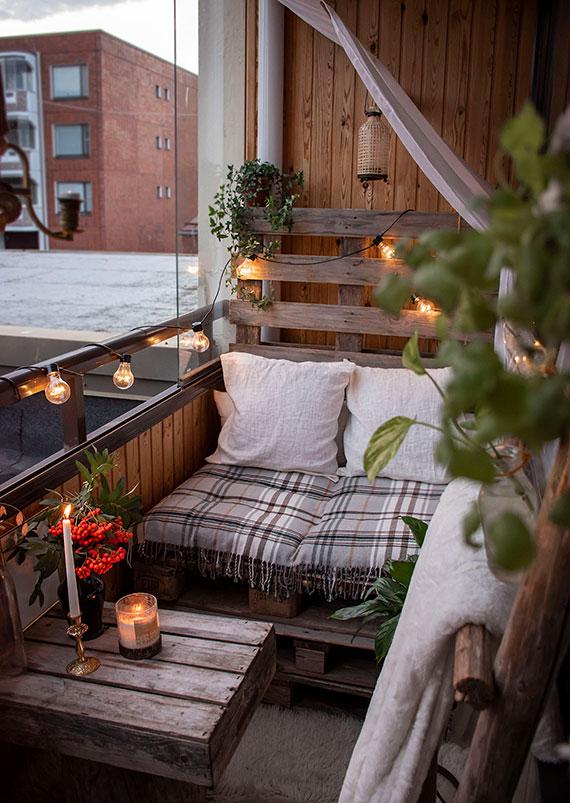 coole balkondekoration im rustikalen stil mit Palettenmöbel, lichterkette und kuscheligen decken